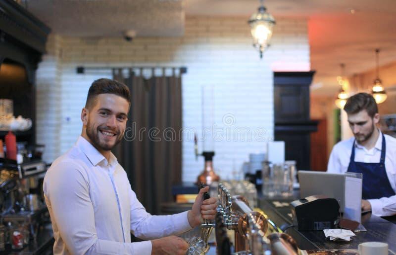 英俊的侍酒者是微笑和填装玻璃用啤酒,当站立在酒吧柜台在客栈时 图库摄影