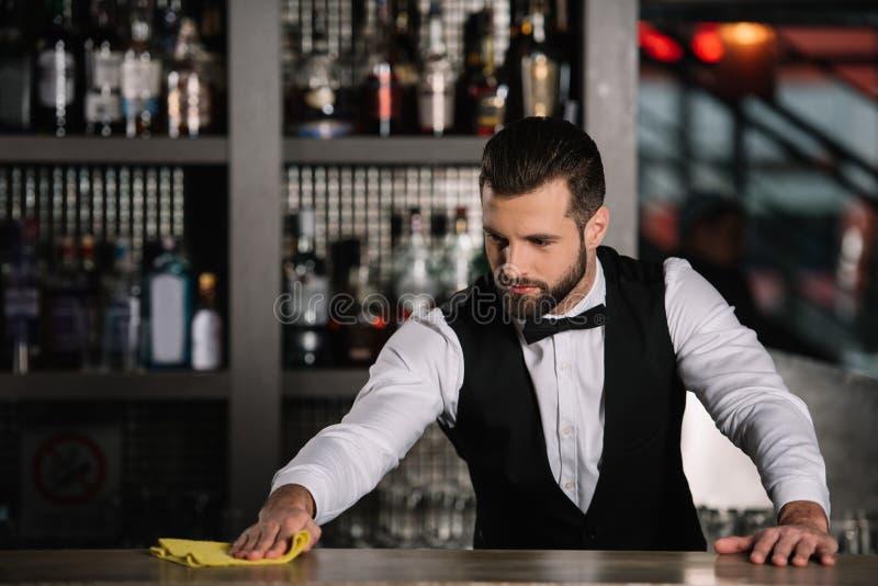 英俊的侍酒者清洁酒吧柜台 免版税库存照片