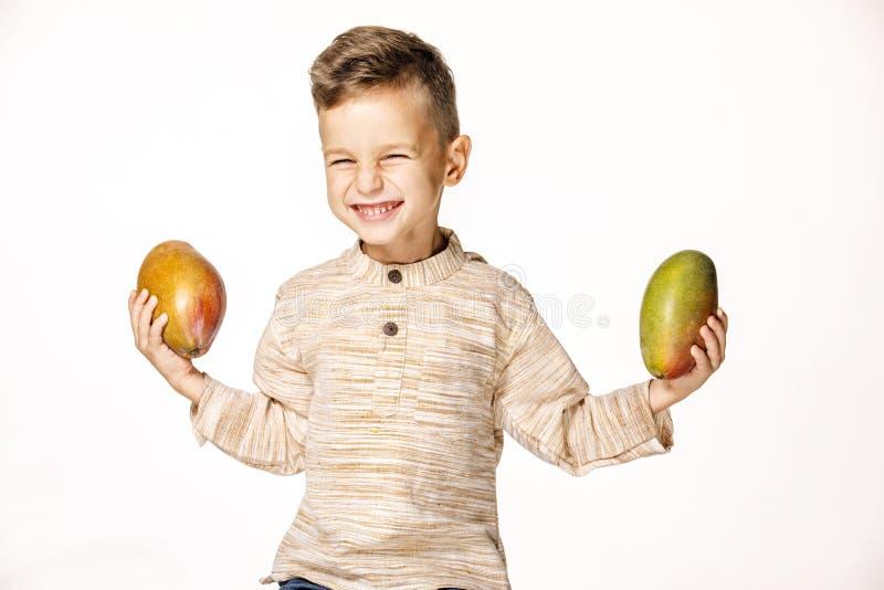 英俊的俏丽的男孩拿着一个芒果 库存图片