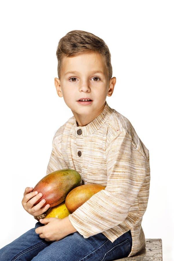 英俊的俏丽的男孩拿着一个芒果 免版税库存照片