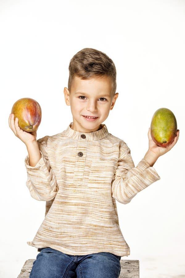 英俊的俏丽的男孩拿着一个芒果 免版税库存图片