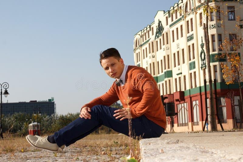 年轻英俊的偶然人坐边路在老城市a 免版税库存图片