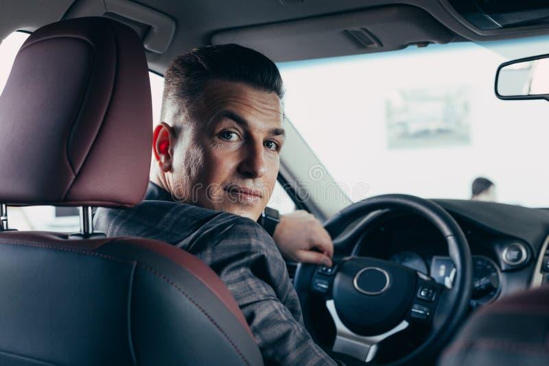英俊的典雅的严肃的人驾驶一辆白色现代汽车 图库摄影