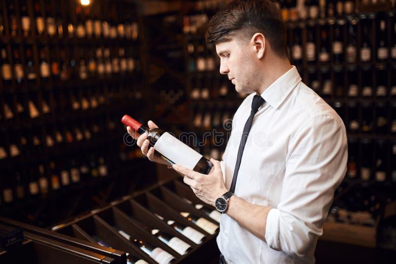 英俊的典雅的选择酒的人帮助的顾客 库存照片