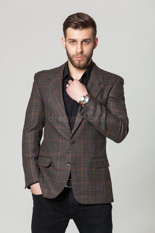 英俊的典雅的年轻人演播室画象棕色夹克的po 库存照片