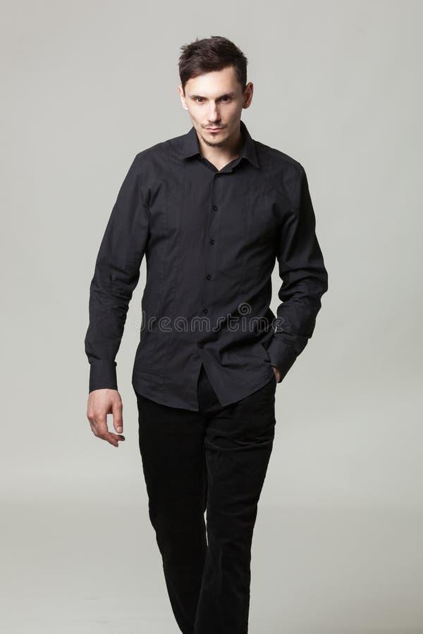 英俊的典雅的年轻人演播室画象黑衣裳的 免版税库存图片