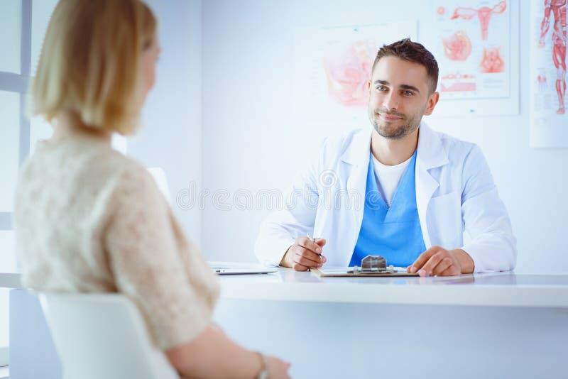 英俊的医生与年轻女性患者谈话并且做笔记,当坐在他的办公室时 免版税库存照片