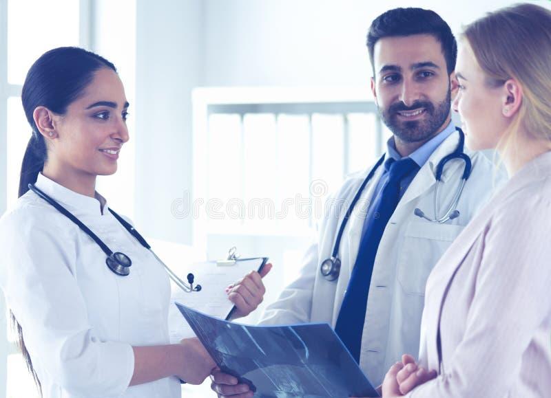 英俊的医生与年轻女性患者谈话并且做笔记,当坐在他的办公室时 库存照片