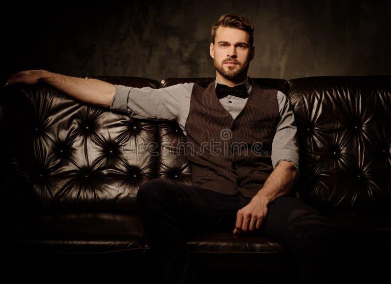 年轻英俊的古板的有胡子的人坐在黑暗的背景的舒适的皮革沙发 库存图片