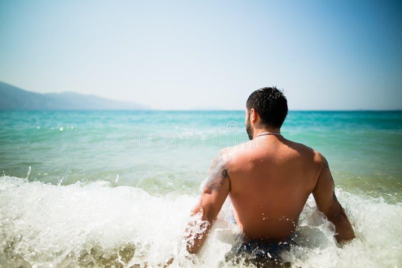 英俊的可爱的肌肉人坐在海滩沙子和放松的海岸 有纹身花刺的晒日光浴英俊的人, spf prot 免版税库存照片