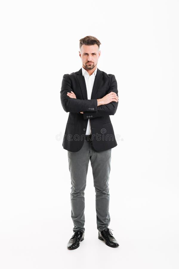 英俊的商人全长画象在摆在c的衣服的 免版税库存图片