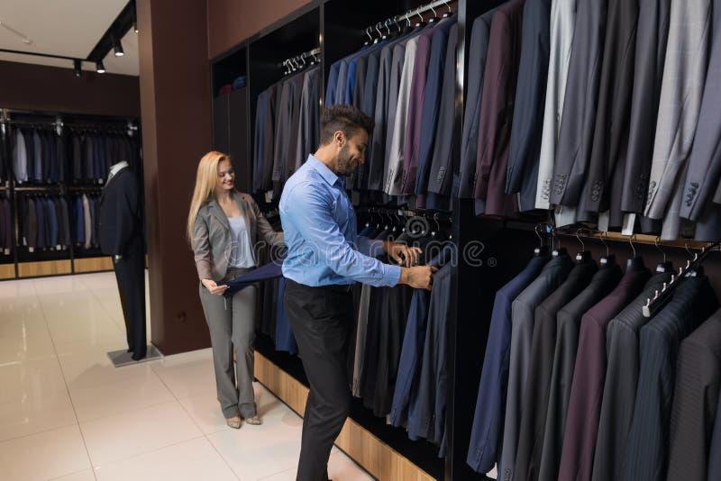 英俊的商人和妇女时尚商店,选择在零售店的顾客衣裳 图库摄影