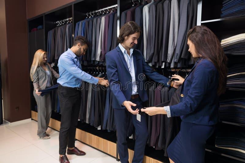 英俊的商人和妇女时尚商店,选择在零售店的顾客衣裳 库存图片