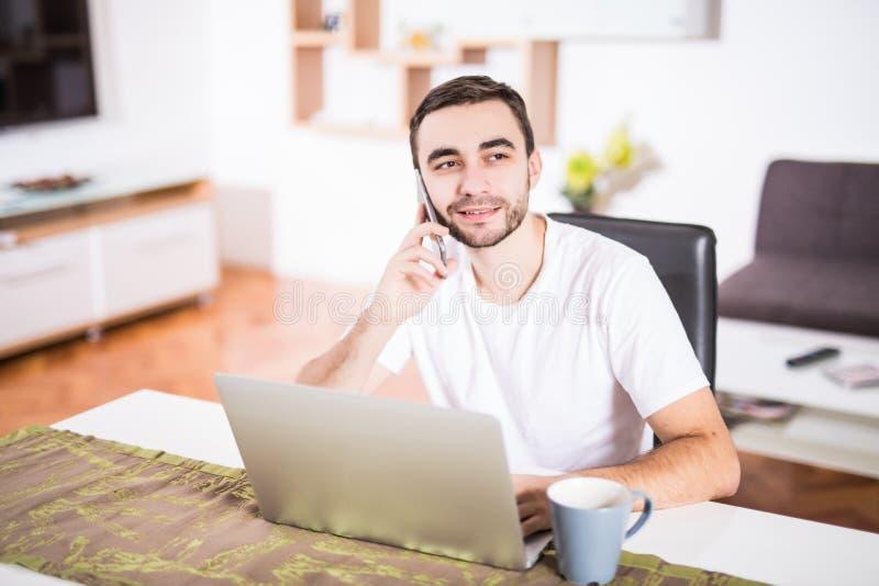 英俊的商人在手机谈话并且微笑着,当使用膝上型计算机在厨房时 免版税图库摄影