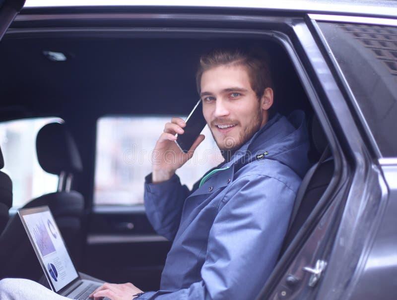 英俊的商人在豪华大型高级轿车,运转坐便携式计算机 库存照片
