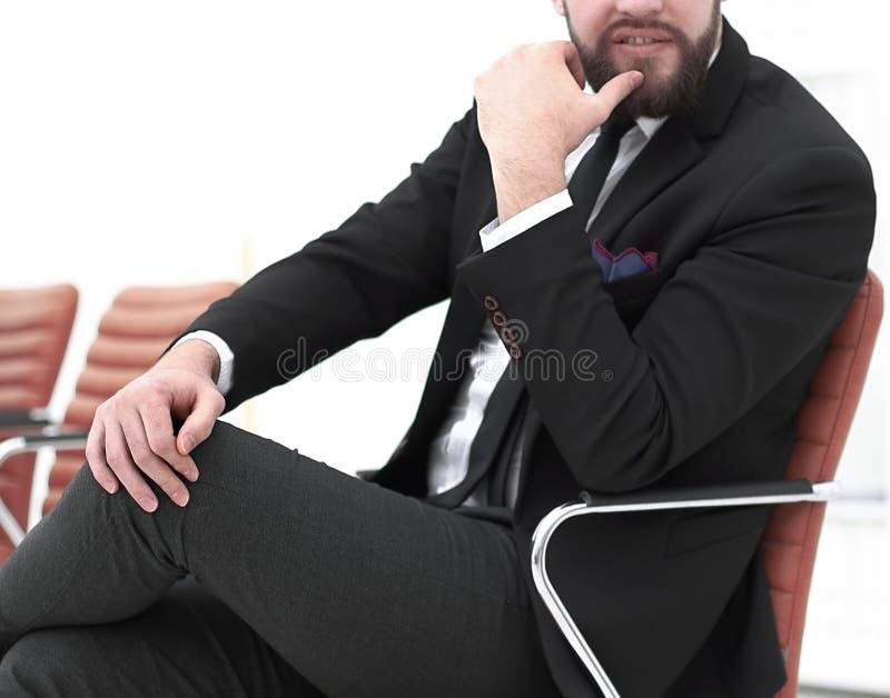 英俊的商人坐一把椅子在会议室 免版税库存照片