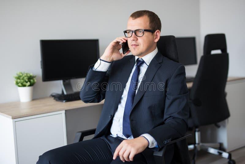 英俊的商人画象谈话由电话在办公室 免版税库存图片