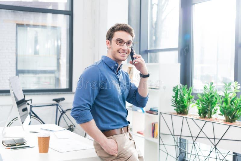 英俊的商人谈话在智能手机 免版税库存图片