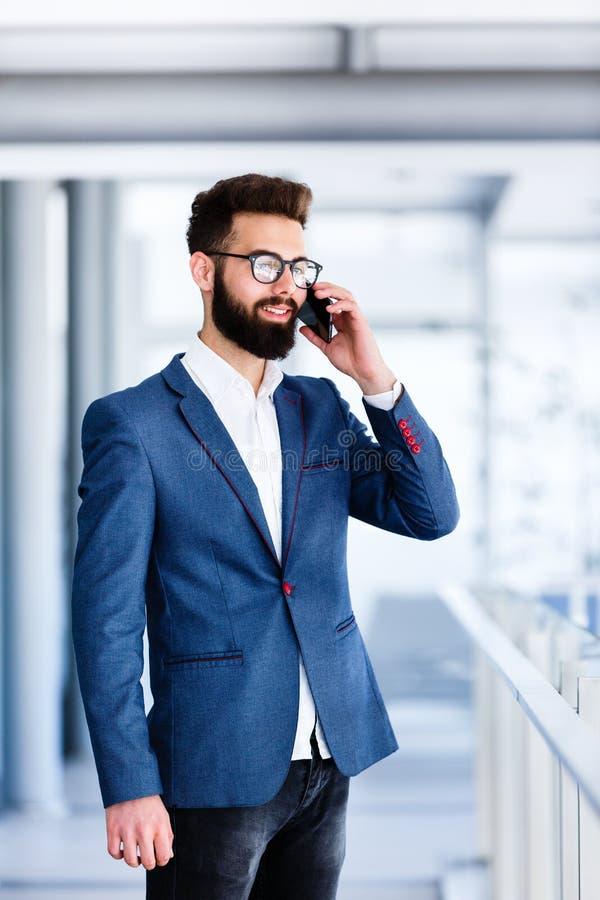 英俊的商人谈话在电话 图库摄影