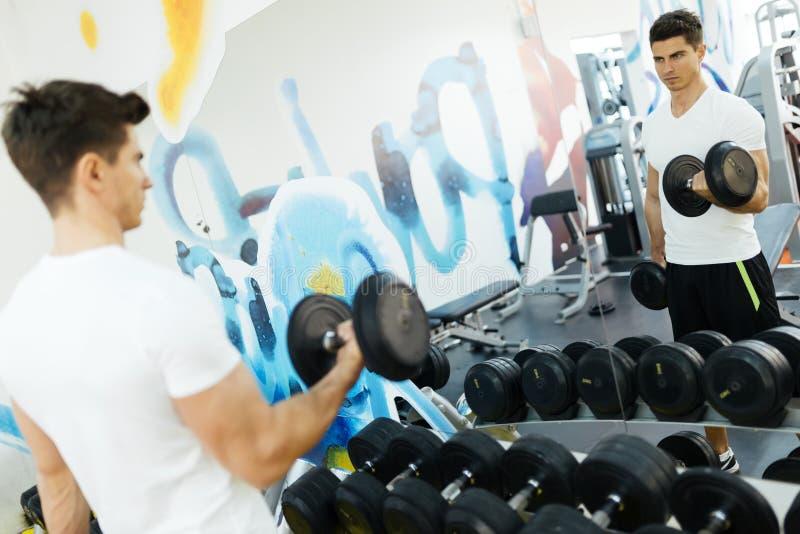 英俊的在健身房的人举的重量 免版税库存图片