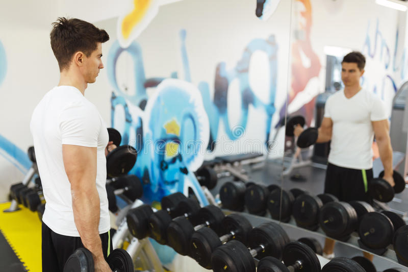 英俊的在健身房的人举的重量 免版税库存照片