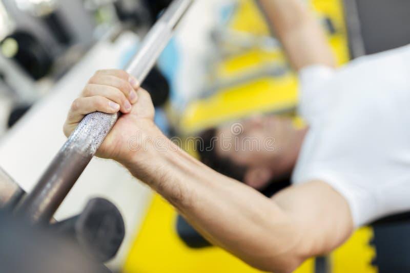 英俊的在健身房的人举的重量 库存照片
