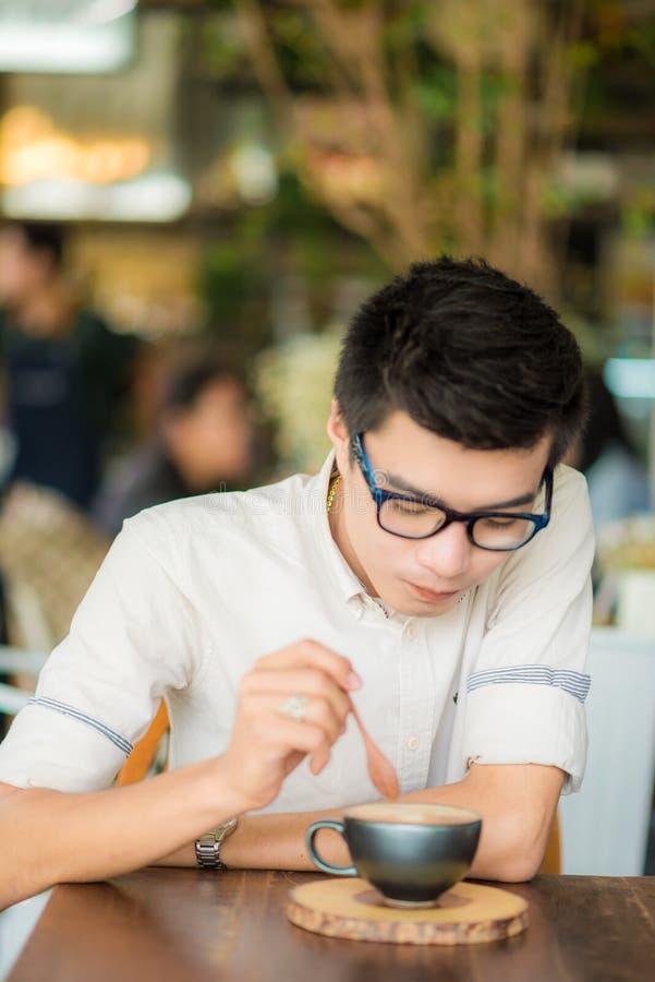 英俊的在咖啡馆艺术的商人饮用的咖啡,亚裔人与 免版税库存图片