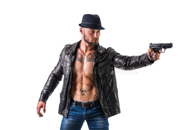 英俊的在指向枪的赤裸肌肉躯干的人佩带的皮夹克照相机,在黑暗的发烟性背景,看 免版税图库摄影