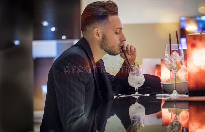 英俊的在酒吧柜台的年轻人饮用的鸡尾酒 免版税库存图片
