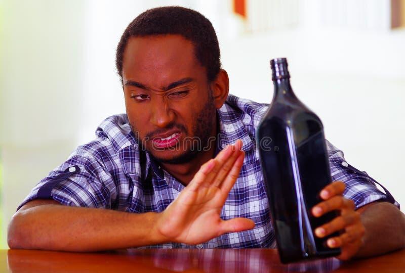 英俊的坐通过酒吧逆说谎的人佩带的白色蓝色衬衣在表示的书桌欲望继续饮用使用 免版税库存照片