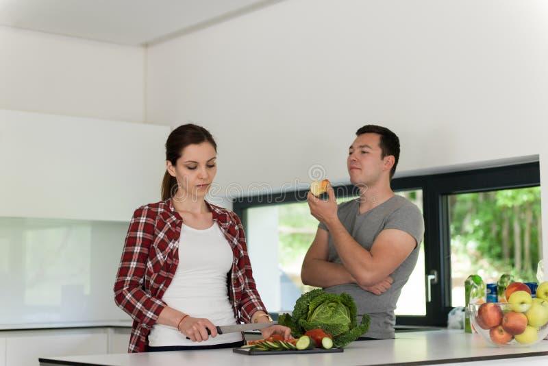 年轻英俊的夫妇在厨房里 图库摄影
