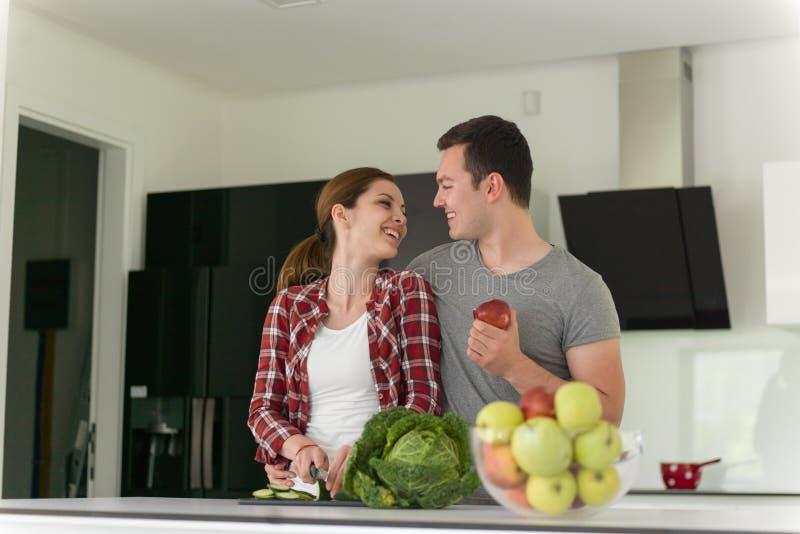 年轻英俊的夫妇在厨房里 库存照片