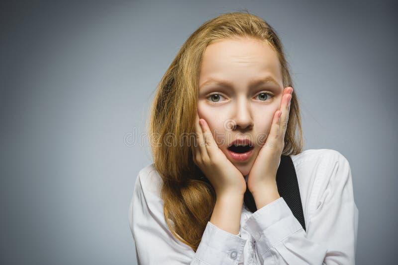 英俊的女孩特写镜头画象有吃惊的表示的,当站立反对灰色背景时 库存图片