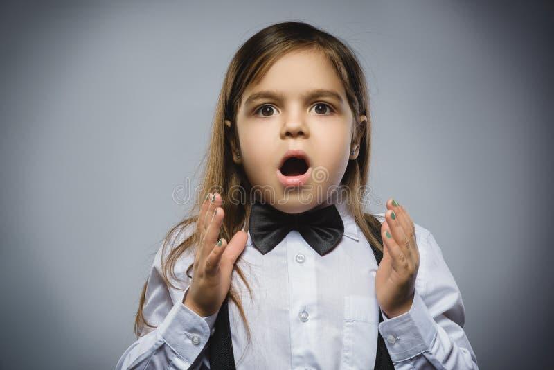 英俊的女孩特写镜头画象有吃惊的表示的,当站立反对灰色背景时 图库摄影