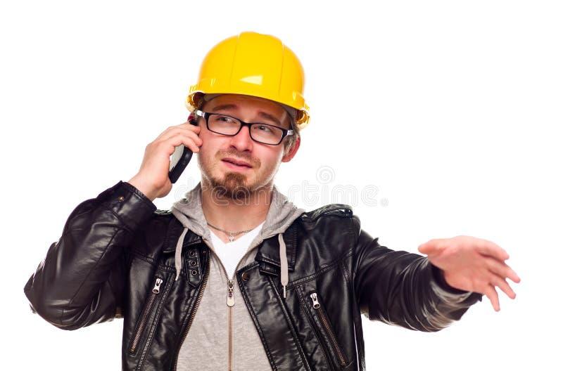 英俊的安全帽人电话年轻人 免版税图库摄影