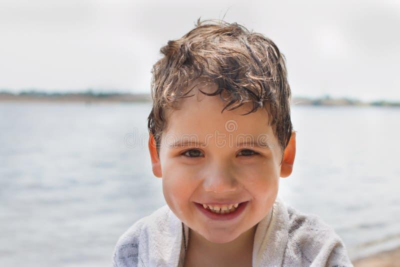 英俊的小男孩微笑靠近河岸对晴天 免版税图库摄影