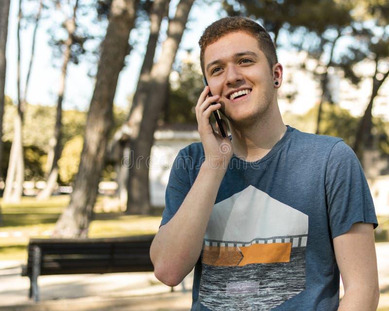 英俊的少年谈话在一个手机户外 免版税图库摄影