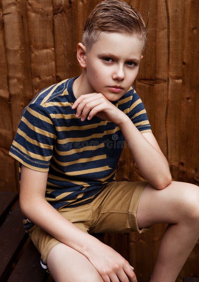 英俊的少年愉快的男孩画象室外在后院 免版税库存照片