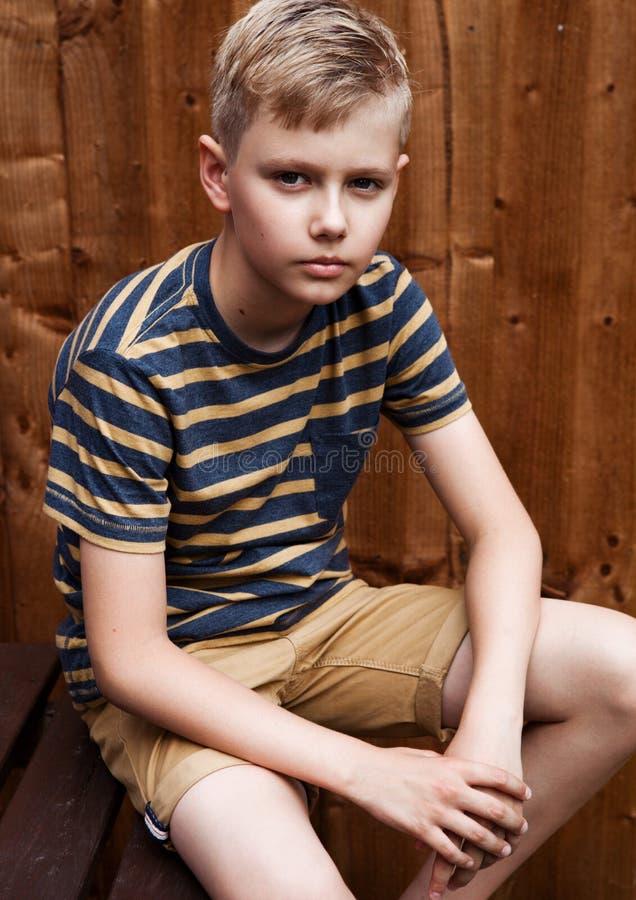英俊的少年愉快的男孩画象室外在后院 免版税库存图片