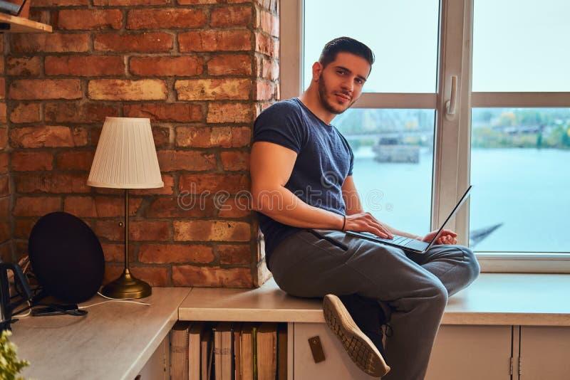 英俊的希腊学生拿着膝上型计算机,当坐在学生宿舍时的一块窗口基石 免版税图库摄影