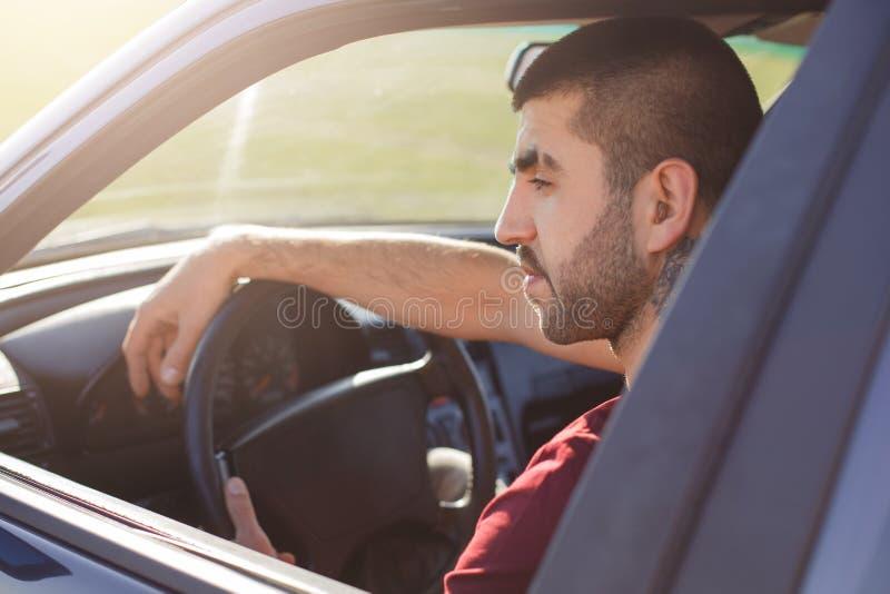 英俊的年轻不剃须的男性斜向一边的射击坐在把他新的汽车引入,有周道,并且concetrated表示,认为abou 图库摄影