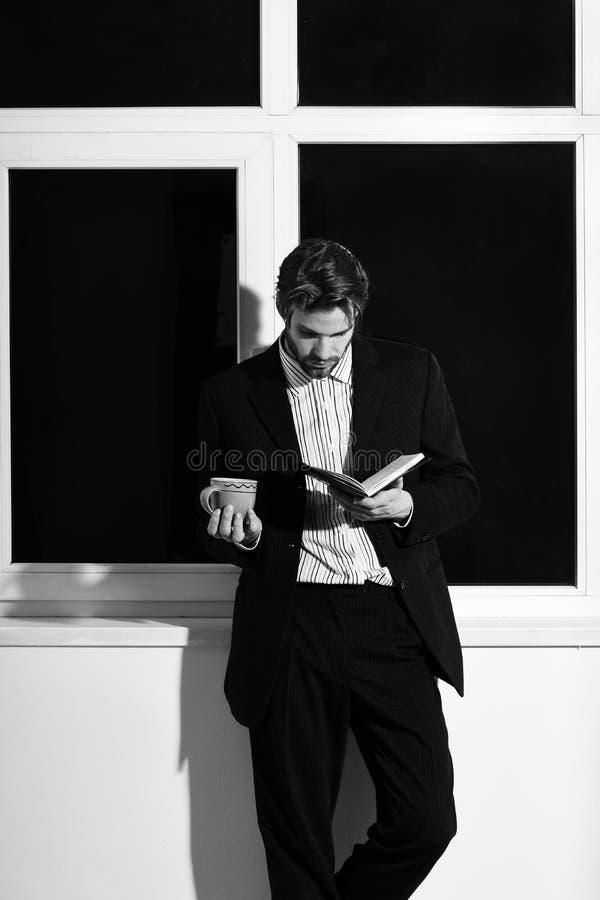 英俊的年轻与时髦的头发的时尚有胡子的商人在站立与黑笔记本的经典衣服近的窗口 图库摄影