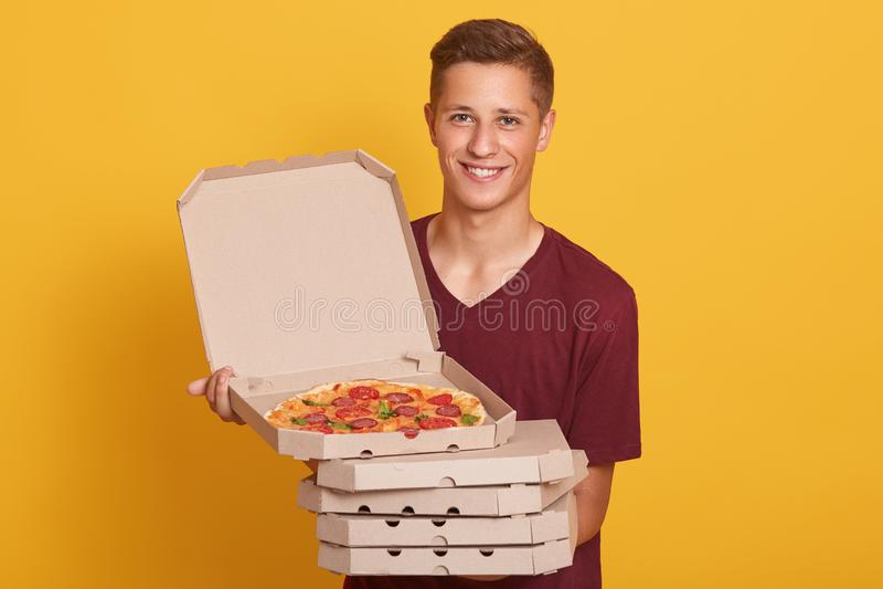 英俊的年轻交付工作者藏品堆比萨箱子,穿戴的偶然T恤杉,看照相机和微笑,显示开放 免版税库存照片