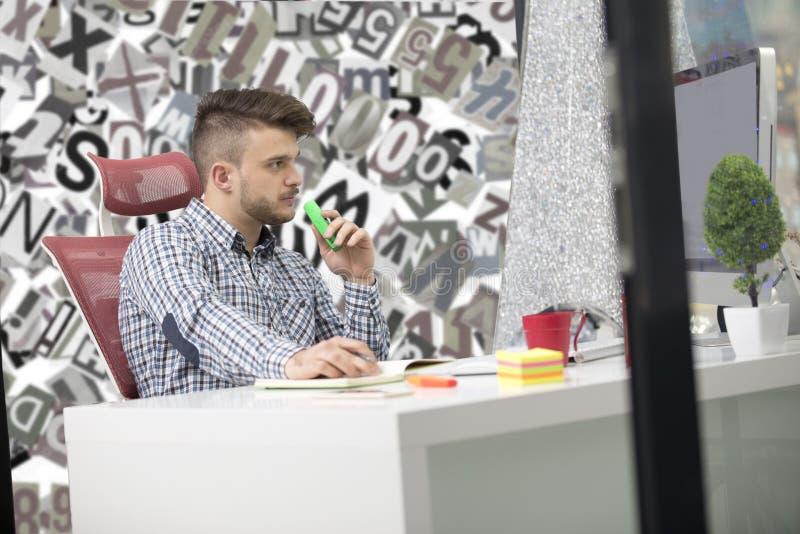 英俊的年轻人与膝上型计算机一起使用在办公室 库存照片