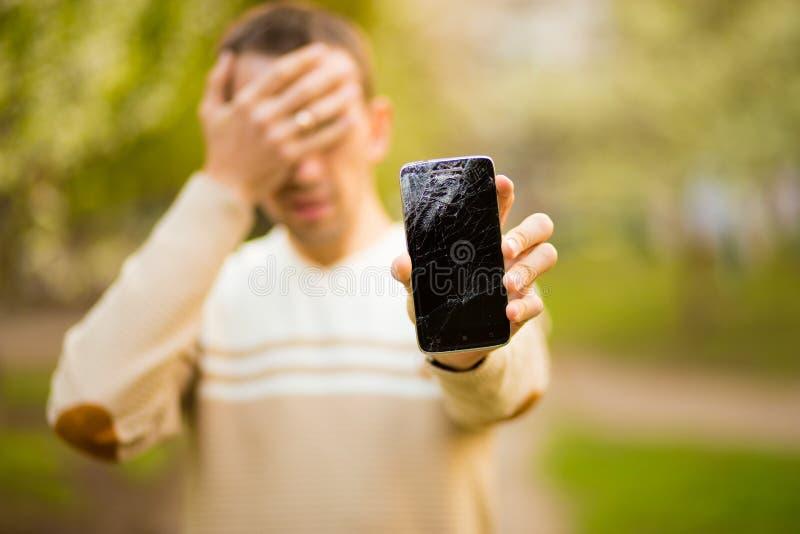 英俊的年轻人举行残破的智能手机屏幕注重了用在头的手,冲击与羞辱和惊奇面孔 库存照片