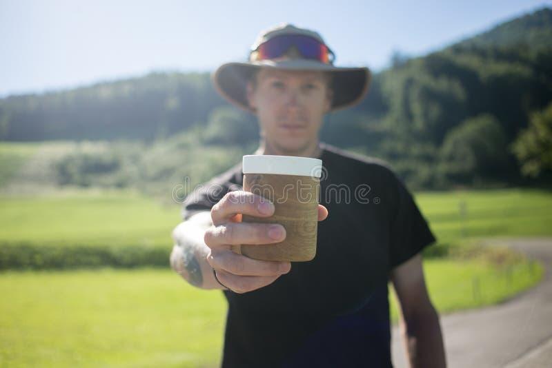 英俊的年轻人喝咖啡在野营 库存照片
