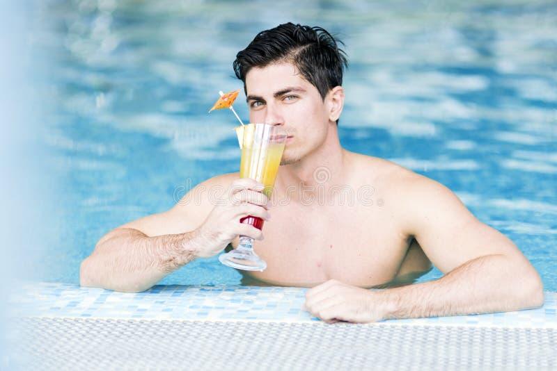 英俊的年轻人在水中的喝一个鸡尾酒 免版税库存照片