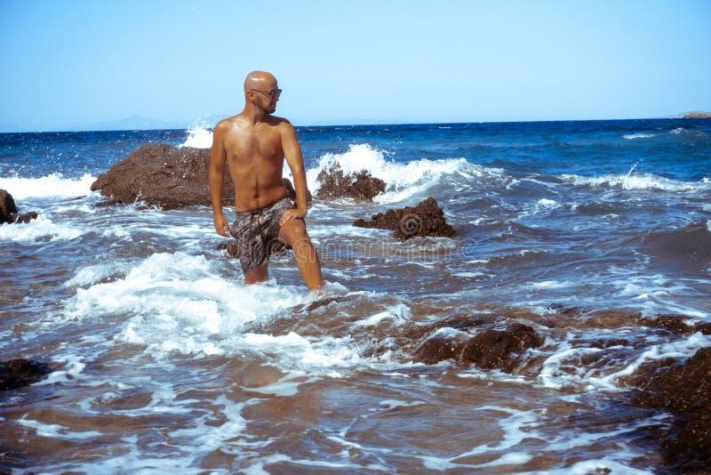 英俊的年轻人在蓝色海 库存照片