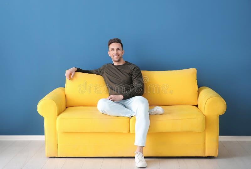 英俊的年轻人坐沙发, 免版税库存照片