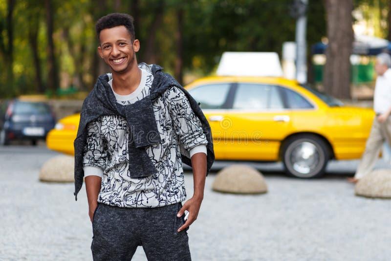 英俊的年轻人混合的族种户外画象,看在照相机,在被弄脏的街道背景 库存图片